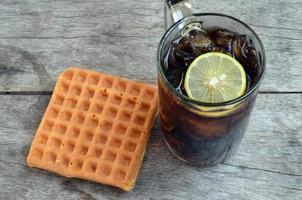 Coca-Cola com limão e waffles doces foto