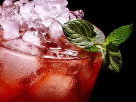 cocktail vermelho e hortelã em fundo escuro
