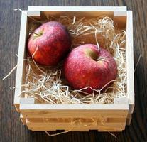 duas maçãs na cesta de madeira foto