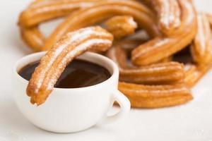 deliciuos churros espanhóis com chocolate quente foto
