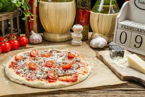 preparando pizza caseira com ingredientes frescos foto