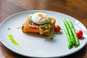 sanduíche com ovo escalfado, presunto de parma e salmão