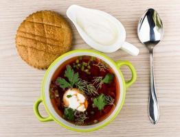 sopa de legumes com beterraba, pão e creme de leite foto