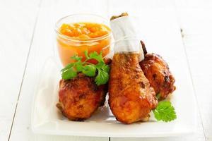 pernas de frango assado com molho barbecue e chutney de manga. foto