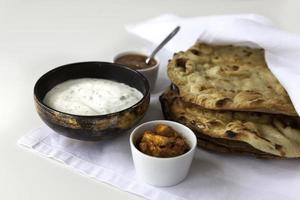 pães indianos planas com chutney de raita e manga foto