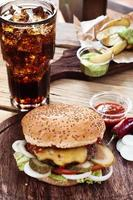 hambúrguer com cola em uma mesa de madeira foto