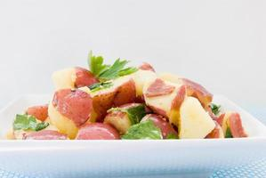 vista frontal saudável salada de batata nova em uma tigela branca foto