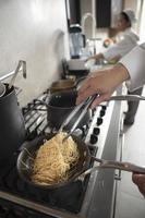 chef prepara espaguete na cozinha foto