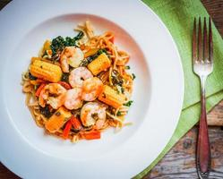 massa italiana com camarões e legumes em fundo de madeira foto