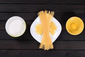 macarrão cru em uma mesa escura, ovo, farinha. vista do topo. foto