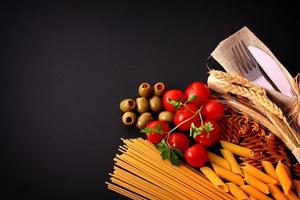 mesa preta sazonal com macarrão e talheres foto