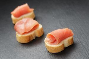 fatias de baguete com salmão ralado no fundo da ardósia foto