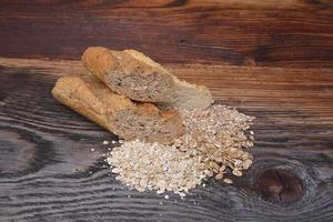 pão e grãos em fundo de madeira foto