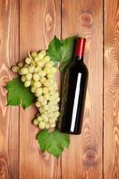 garrafa de vinho tinto e cacho de uvas brancas