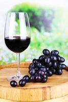 vinho saboroso e uva madura sobre fundo verde natureza foto