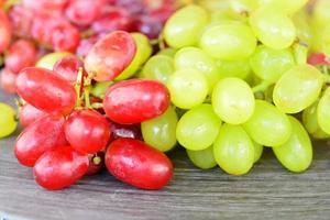 uvas naturais verdes e vermelhas em uma placa de madeira foto