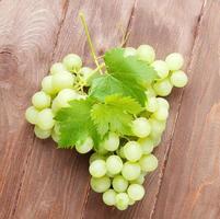 cacho de uvas na mesa de madeira foto