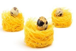 ninho de macarrão ovo italiano três no fundo branco. foto