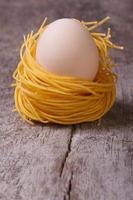 ninho de macarrão seco com ovos de galinha verticais foto