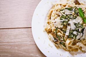 prato vegetariano delicioso de macarrão e salsa na mesa de madeira foto
