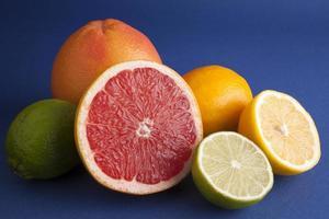 frutas cítricas frescas sobre fundo azul.