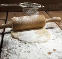 massa, com amontoado de farinha, sendo enrolada com rolo