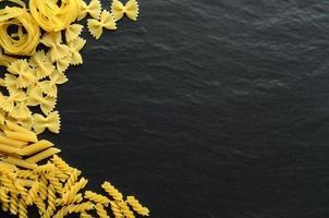 diferentes tipos de macarrão em um fundo escuro foto