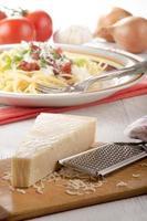 queijo parmesão e ralador na madeira foto