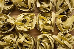 massa de tagliatelle italiano em fundo de madeira foto