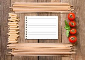 macarrão, tomate e manjericão em fundo de madeira foto