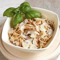 porção de esparguete à bolonhesa com folhas de manjericão foto