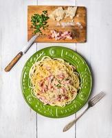 espaguete à carbonara em chapa verde sobre fundo branco de madeira foto