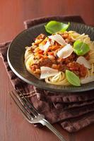 macarrão italiano esparguete à bolonhesa com manjericão na mesa rústica foto