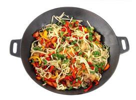 macarrão com legumes no wok isolado no branco foto