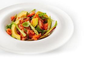 salada de legumes com truta em fundo branco foto