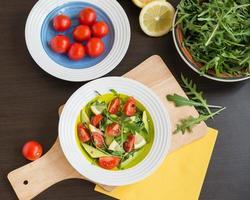 comida saudável. salada fresca de rúcula, tomate cereja, abacate foto