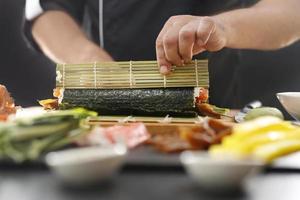 mestre de sushi prepara futomaki