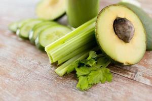 close-up de legumes e copo de suco verde fresco foto