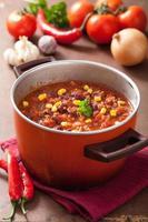 chili com carne mexicana em panela rústica vermelha com ingredientes foto