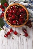 cerejas vermelhas em uma tigela de madeira vista vertical acima, rústico foto