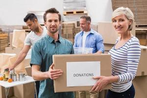 dois voluntários segurando uma caixa de doações
