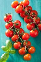 tomate cereja sobre fundo turquesa foto