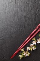 pauzinhos de sushi japonês e flor de sakura foto
