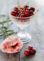 cereja em um vaso com flores na mesa de madeira foto