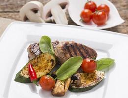 grelhados de carne, com legumes frescos no prato foto