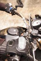 mão de motociclista repousa sobre o volante da motocicleta foto