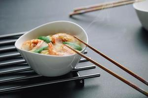 macarrão quente com camarões em um fundo preto foto