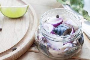 fatias de cavala marinada com cebola em uma jarra foto