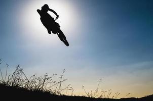 silhueta de salto de motocross com céu azul foto