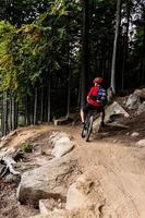 motociclista da montanha andando de bicicleta na floresta de outono foto
